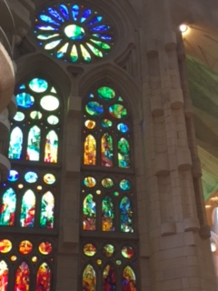 Stained glass amidst stonework in high-ceilinged church.